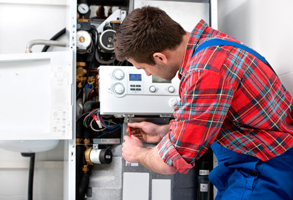 expert plumber with Pristine Plumbing servicing boiler system in home