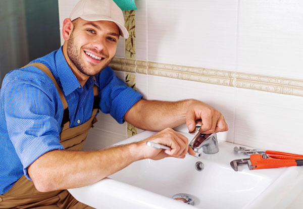 photo of edmonton plumber fixing homeowners bathroom leaking faucet.